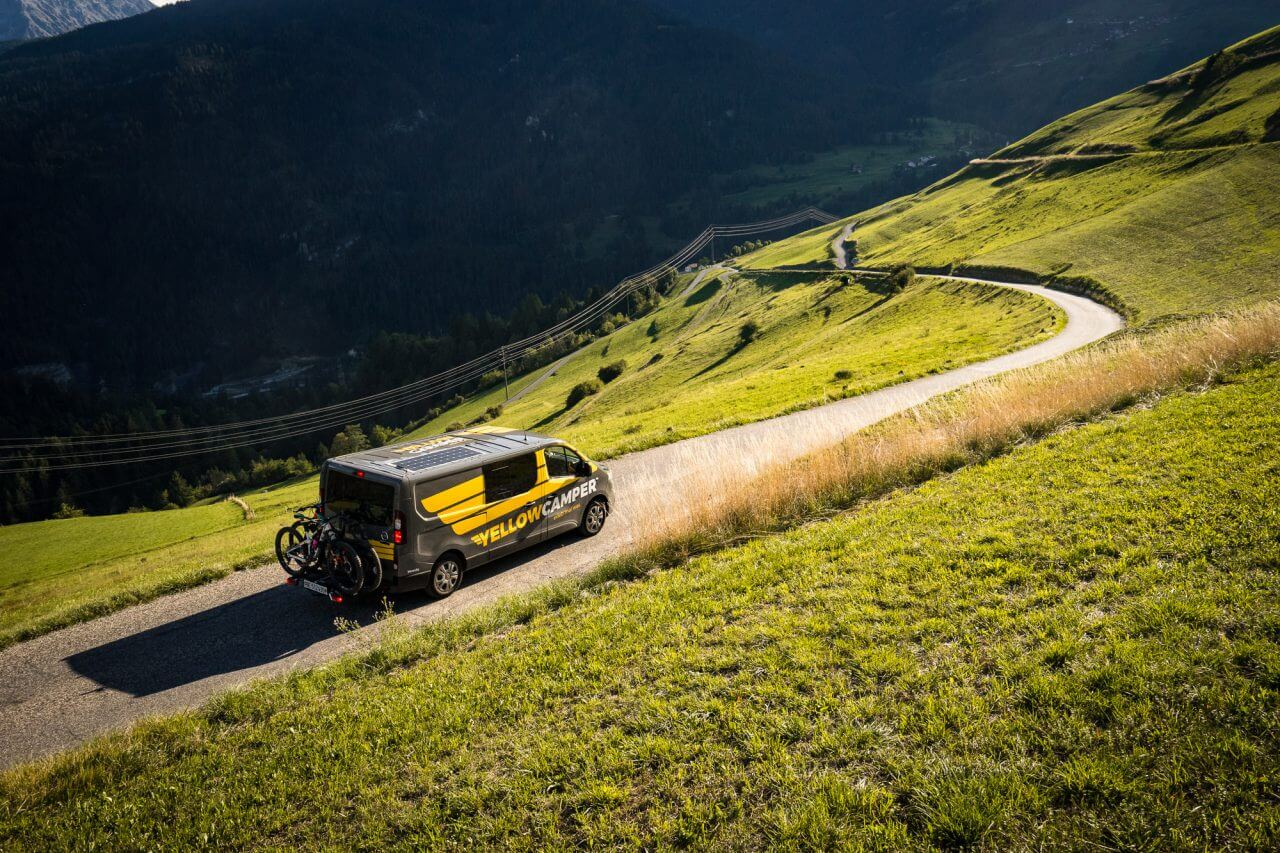 yellowcamper campervan on a road in switzerland