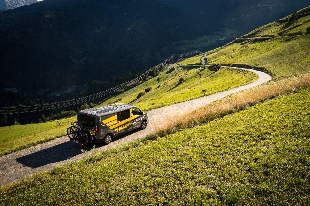 yellowcamper campervan on a road in switzerland